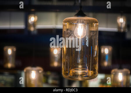 Vintage decorative light lamp bulb glowing on the ceiling indoors - Stock Photo