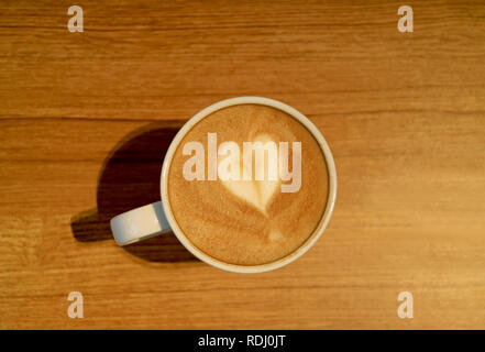 Heart Shaped Latte Art of Hot Cappuccino Coffee with Latte Art in a White Cup Served on Wooden Table - Stock Photo