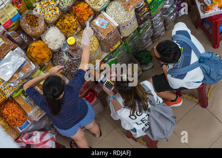 Danang, Vietnam - October 14, 2018: a young woman traveler, accompanied by a man, counts expenses on calculator in Cho Han market. - Stock Photo