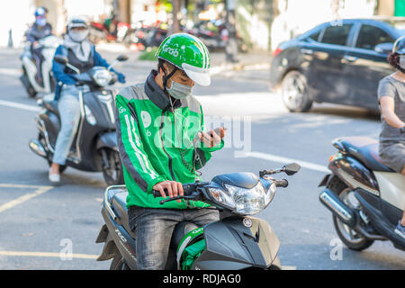 Danang, Vietnam - October 14, 2018: A young man on a scooter, wearing a Grab green helmet and jacket, looks at his mobile phone. - Stock Photo