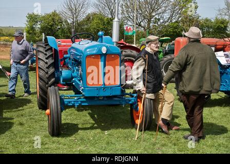 Visitors chat next to a vintage blue tractor at the Anglesey Vintage Rally, Anglesey, North Wales, UK, May 2010 - Stock Photo