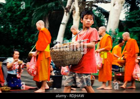 Luang Prabang / Laos - JUL 06 2011: monks during their early morning round around the town to collect their alms - Stock Photo