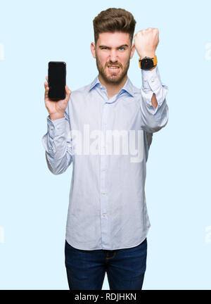 Young handsome man business showing smartphone screen annoyed and frustrated shouting with anger, crazy and yelling with raised hand, anger concept - Stock Photo