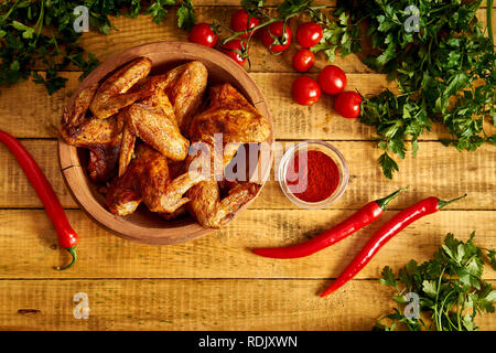Delicious grilled chicken wings in wooden bowl with spices and vegetables on old wooden table. - Stock Photo