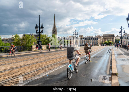 Bordeaux, France - July 22, 2018: Scenic view of Pont de Pierre Bridge with cyclists a rainy day of summer - Stock Photo