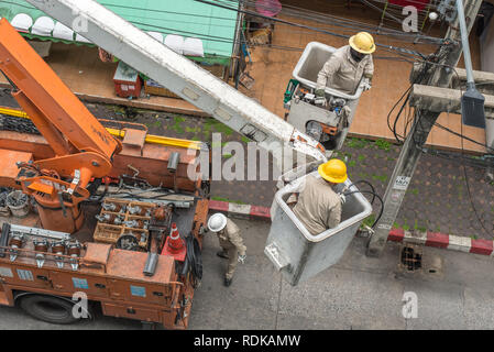 Bangkok, Thailand - July 22, 2018: electricians in uniform repair an electric pole being on aerial work platforms. - Stock Photo