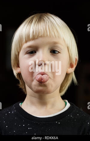 Strong willed little boy being naughty, showing his tongue. Playful childhood, little rebel, headstrong, stubborn child concept. - Stock Photo
