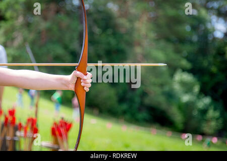 Archer holds his bow aiming at the target outdoor activity