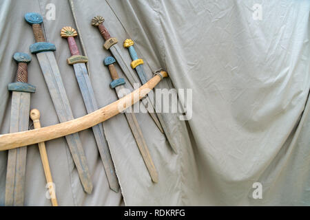 Wooden handmade swords hanging on the rope on grey fabric background. Medieval weapons for close combat displayed on grey fabric texture - Stock Photo