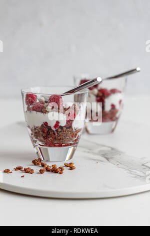 Two glasses of layered granola and yogurt with raspberries on a marble tray on a white background - Stock Photo