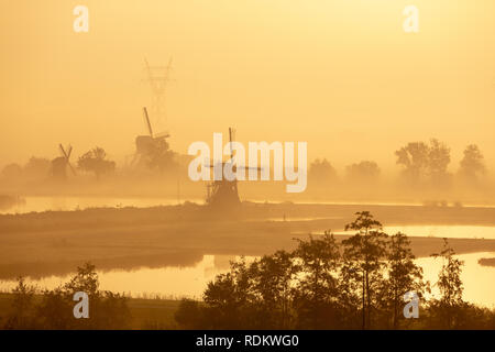 Historic old windmills in a foggy morning in the Doespolder in the village of Leiderdorp in the Netherlands. - Stock Photo
