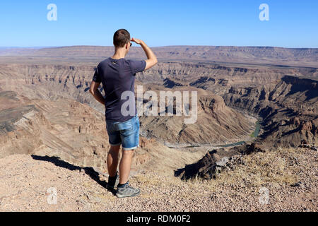 a man looks out over the Fish River Canyon - Namibia Africa - Stock Photo