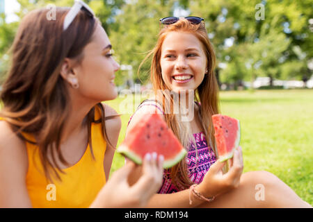 teenage girls eating watermelon at picnic in park - Stock Photo