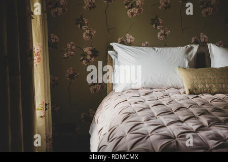 Interior view of bedroom with curtains and wallpaper with floral pattern, pale pink quilt and white pillows on double bed. - Stock Photo