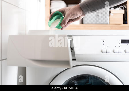 person using dosing aid to pout laundry detergent powder into washing machine