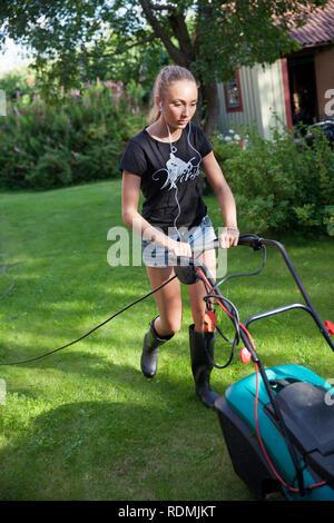 Teenage girl mowing lawn in backyard - Stock Photo
