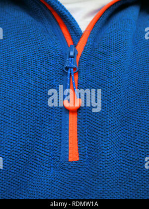 Orange Zip Fastner With Toggle or Zipper on a Man's Blue Sweatshirt Clothing - Stock Photo