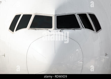 Close front outside view of a white big jet plane cockpit. - Stock Photo
