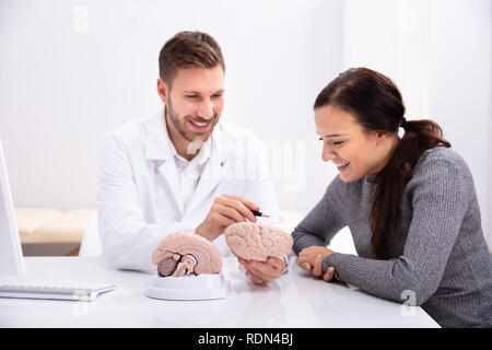 Doctor Explaining Details Of Human Brain To Happy Woman With Model - Stock Photo