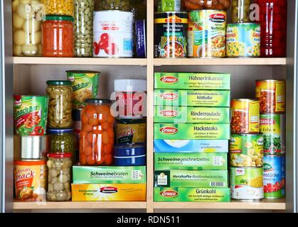 Cupboard filled with various packaged foods in glass jars and tin cans - Stock Photo