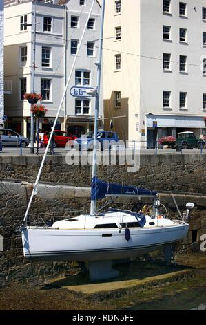 Boat lying dry in the marina at low tide, main port, St. Peter Port, Guernsey, Channel Islands, Europe - Stock Photo