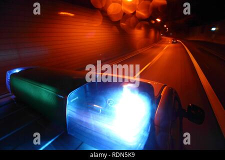 Blue light response driving, highway police patrol car in a highway tunnel, A40 motorway or Ruhrschnellweg, Essen - Stock Photo