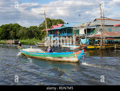 Local fishermen in a fishing boat passing houses on stilts in floating village in Tonle Sap lake. Kampong Phluk, Siem Reap, Cambodia, Asia - Stock Photo