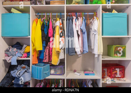 Open wardrobe with things and toys in the children's room - Stock Photo