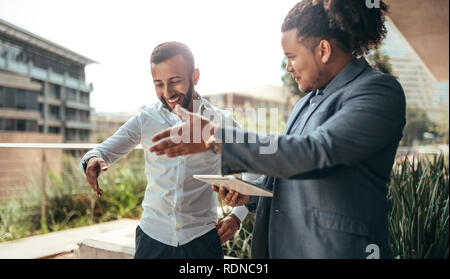 Two trendy businessmen talking and laughing casually outside, talking using hand gestures to show directions or being expressive - Stock Photo