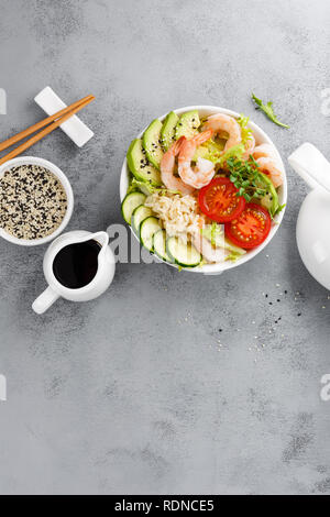 Hawaiian poke bowl with shrimps, rice and vegetables, healthy Buddha bowl with prawns, rice, avocado, cucumber, tomato and lettuce. Top view - Stock Photo