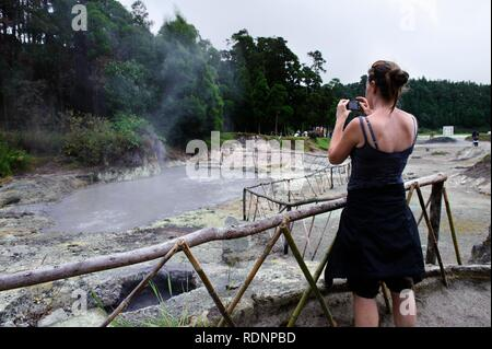 Woman taking pictures of fumaroles at Lagoa das Furnas on the island of Sao Miguel, Azores, Portugal - Stock Photo