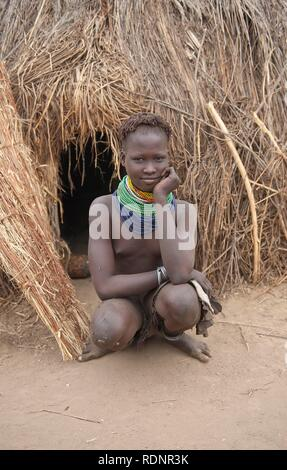 Nyangatom, Bume or Buma girl with bead necklaces in front of her hut, Omo Valley, Ethiopia, Africa - Stock Photo