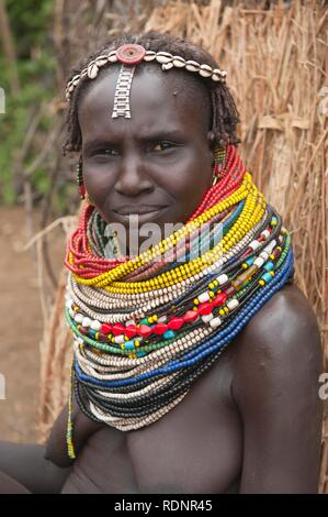 Nyangatom, Bume or Buma woman with bead necklaces in her village, Omo Valley, Ethiopia, Africa - Stock Photo