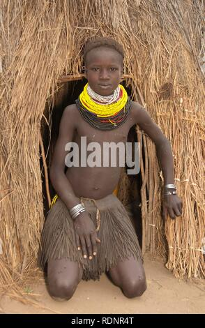 Nyangatom, Bume or Buma girl in front of her hut, Omo Valley, Ethiopia, Africa - Stock Photo