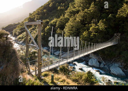 The beginning of the Rob Roy Glacier Track leads hikers over the Matukituki River via a swing bridge into a beech forest in the Matukituki Valley near - Stock Photo