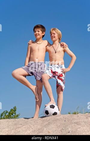 Two boys with a football on the beach, Timmendorf, Poel island, Mecklenburg-Western Pomerania, Northern Germany - Stock Photo