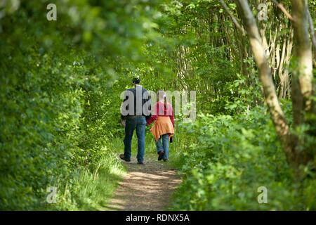 Man walking with a little girl into the woods, posed scene - Stock Photo