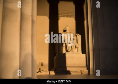 WASHINGTON DC, United States - Early morning at the Lincoln Memorial in Washington DC. Sitting on the western end of the National Mall, it commemorates the 16th president of the United States, Abraham Lincoln. This photo was taken around the spring solstice. With the sun rising directly in the east, the light briefly shines directly onto the massive statue of Lincoln that sits deep inside the building. - Stock Photo