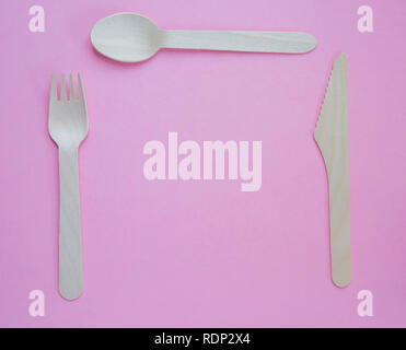 A flat lay of sustainable wooden cutlery including a knife, fork and spoon set for dinner in a place setting and on a pink background wit copy space - Stock Photo