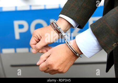 Man in a suit and in handcuffs - Stock Photo
