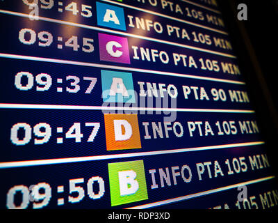 Close-up details of a typical airport information board with mutiple airlines hours departure gates and insignia for the boarding gate - Stock Photo