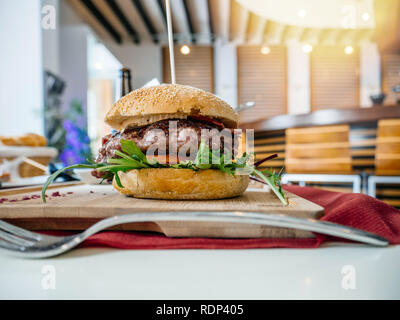 Delicious burger in restaurant cafe side view with all the ingredients, organic bun bread, big fresh meat, lettuce salad, tomato - defocused background  - Stock Photo