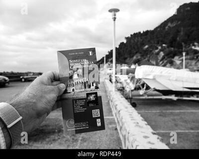 Port de Valldemosa, Palma de Malloca, Spain - May 10, 2018: Man holding pov the touristic guide of the Santa Maria of Palma Cathedral in the parking of Port de Valldemosa - black and white - Stock Photo