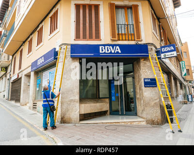 FELANITX, PALMA DE MALLORCA, SPAIN - MAY 10, 2018: Worker preparing to clean the facade insignia logotype of the Spanish BBVA bank while installing fiber optic internet cable above entrance - Stock Photo
