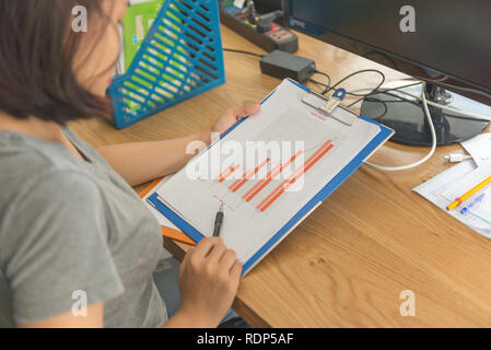 Rear view photo of Asian employee checking sales report in office room - Stock Photo