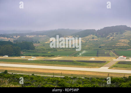 Aerial view of agricultural fields, local airport runway and hills covered in fog, Moss Beach, California - Stock Photo