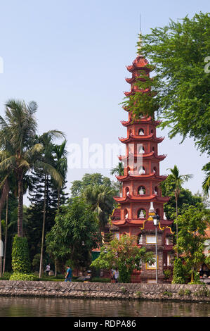 Chua Tran Quoc Temple Pagoda, the oldest Buddhist temple in Hanoi, and gardens with tourists walking around, Hanoi, Vietnam - Stock Photo