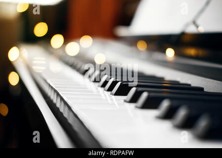 piano keys with beautiful yellow lights bokeh in background