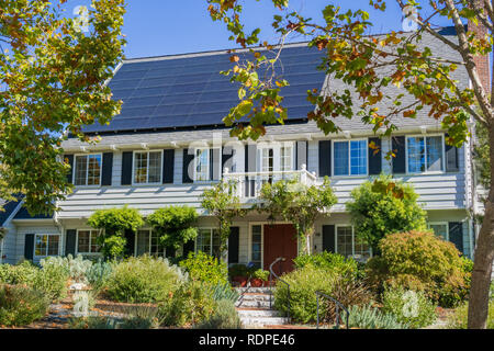 House with solar panels on the roof in a residential neighborhood of Oakland, in San Francisco bay on a sunny day, California - Stock Photo