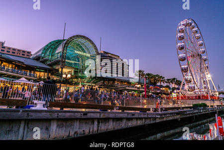 23rd December 2018, Sydney Australia: Harbourside shopping centre view at dusk in Darling Harbour with Ferris wheel and people in Sydney NSW Australia - Stock Photo